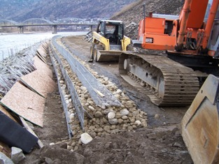MSE wall constructed above vegetated riprap, cobbles were later placed over wooden sheets